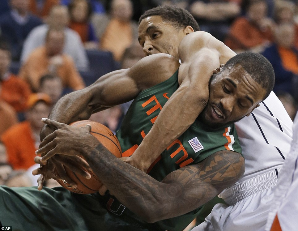 Hustle: Miami forward Erik Swoope (front) struggles for a rebound with Virginia guard Malcolm Brogdon during the first half of this NCAA college basketball clash