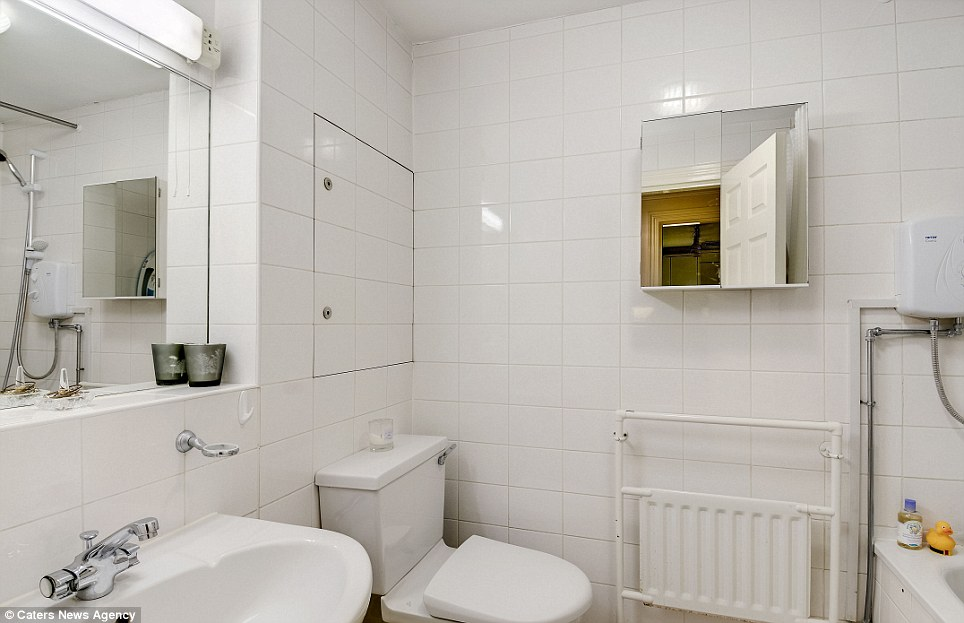 The bathroom clearly utilises an extensive use of mirrors to give it the impression of more space. The bathroom features a small sink, bath and toilet with tiled walls