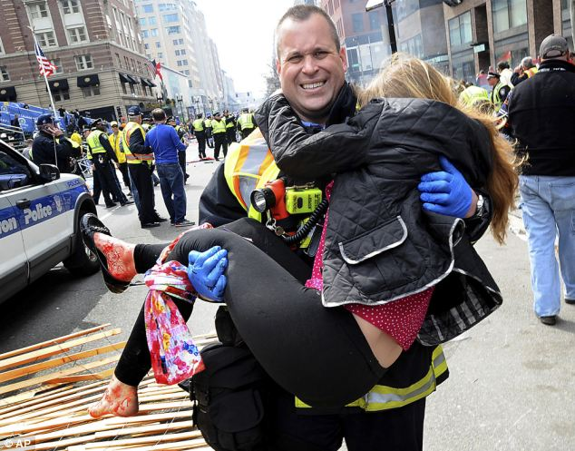 Boston Firefighter James Plourde carries an injured girl away from the bomb scene near the finish line