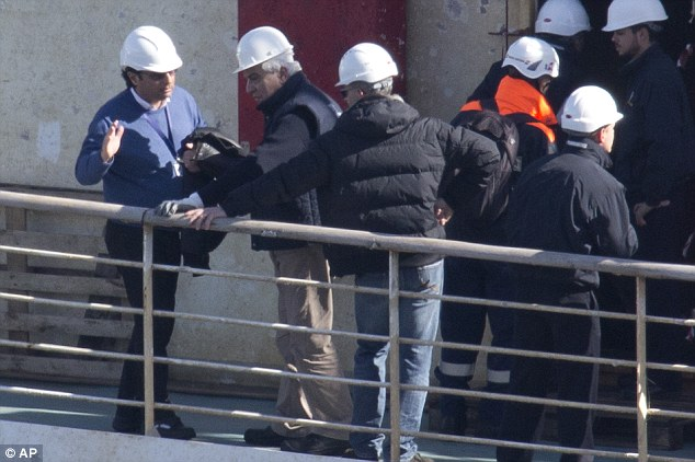 Back on board: Costa Concordia captain Francesco Schettino (left) stands on the upper deck of the doomed ship on his first visit since the disaster that claimed 32 lives two years ago