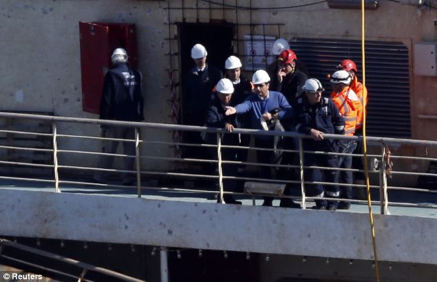 Looking for clues: Captain Schettino stands aboard the Costa Concordia, and appears to point something out to the team with him