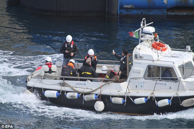 Francesco Schettino (right) takes images with his cell phone as he leaves the shipwrecked cruise liner