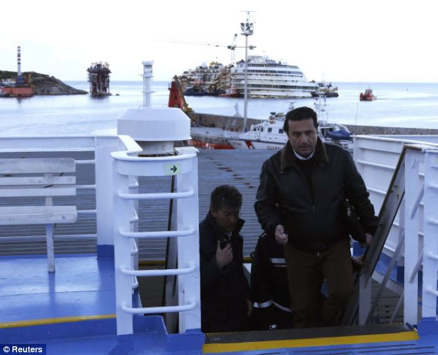 Setting sail: Schettino (front) climbs aboard a ferry as he leaves Giglio harbour with the crashed Costa Concordia in the background