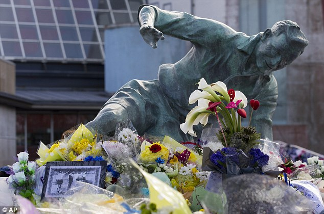 Floral tribute: Flowers are seen by a statue of Finney at Preston's Deepdale ground