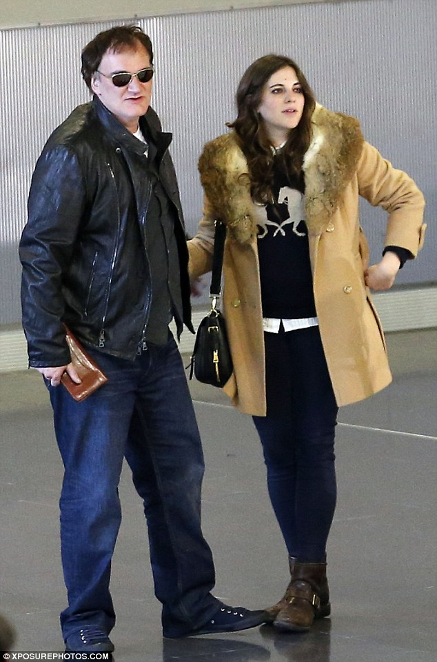 Touchy feely: The Django Unchained director kept a hand on the mystery brunette at the Charles De Gaulle  airport terminal
