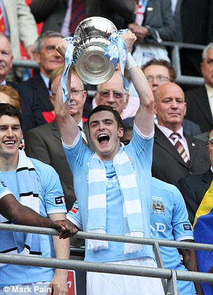 Silverware: Johnson lifts the FA Cup after City defeat Stoke at Wembley