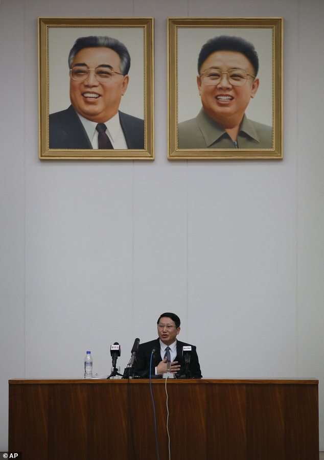Interrogated: The missionary speaks under the portrait of late leaders Kim Il Sung and Kim Jong Il during a news conference in Pyongyang