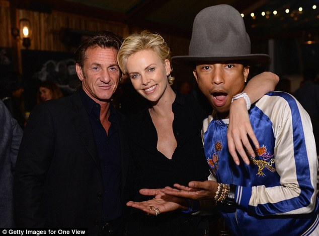 It's REALLY them! Pharrell Williams looks star struck by loved up couple Sean Penn and Charlize Theron at an event celebrating his Oscar-nominated single Happy