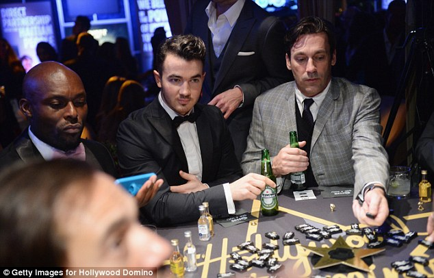 Don would be proud: Mad Men actor Jon Hamm  sups a beer as he plays dominoes with musician Kevin Jonas and actor Jimmy Jean-Louis at the 7th Hollywood Domino and Bovet 1822 Gala