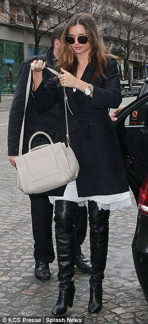 Tasteful: Miranda matched her boots with a smart black coat and minimal accessories, primarily a pair of large sunglasses and a white leather handbag