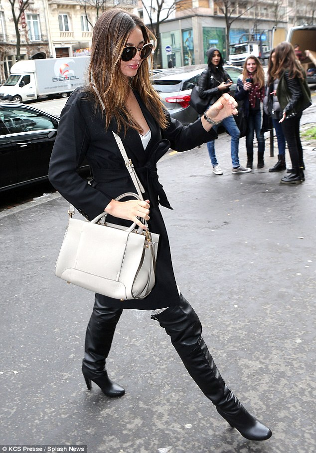 Catching the eye: Onlookers watch as Miranda cuts a path across the street after leaving the Paris office of French fashion designer Sonia Rykiel