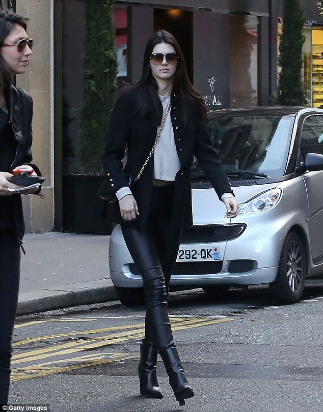 Sleek and chic: The beautiful brunette donned a dark jacket with gold buttons, teamed with leather pants, an off-white long sleeved shirt, and black high heeled boots