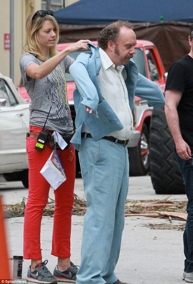 Suiting up: An assistant was seen putting on Paul's blue jacket on Thursday in Miami Beach