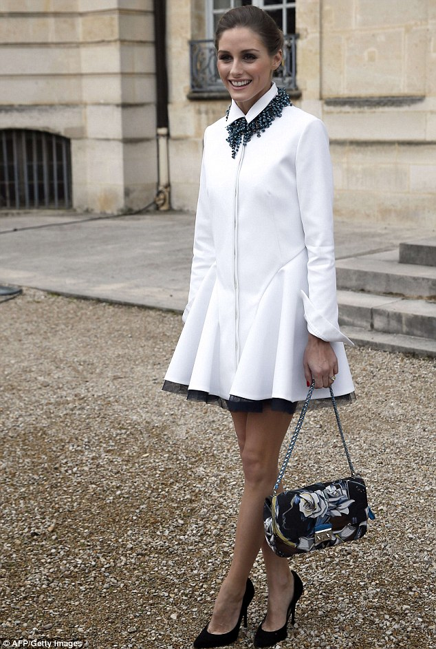 Pretty: Olivia looked stunning in her white coat and floral handbag for the fashion show