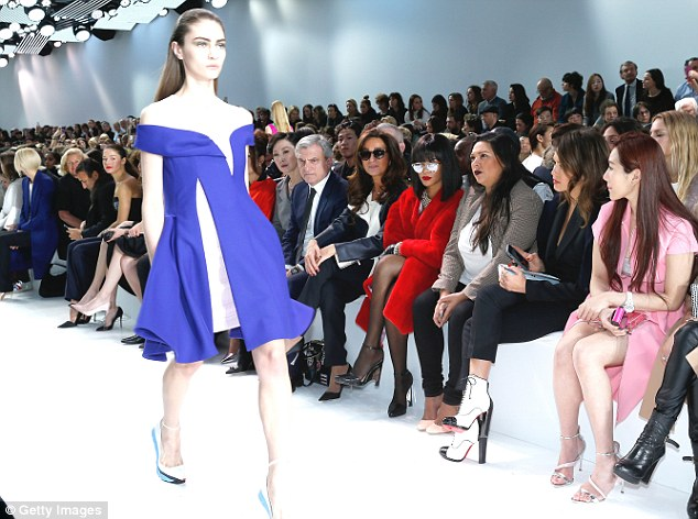 Model strut: The VIPs looked on as a model walked the catwalk for the Womenswear Fall/Winter 2014-2015 collection