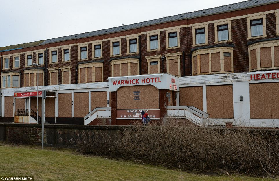 In decline: The once-grand Warwick Hotel sits boarded up, MDF panels covering its windows and doors to deter vandals and intruders
