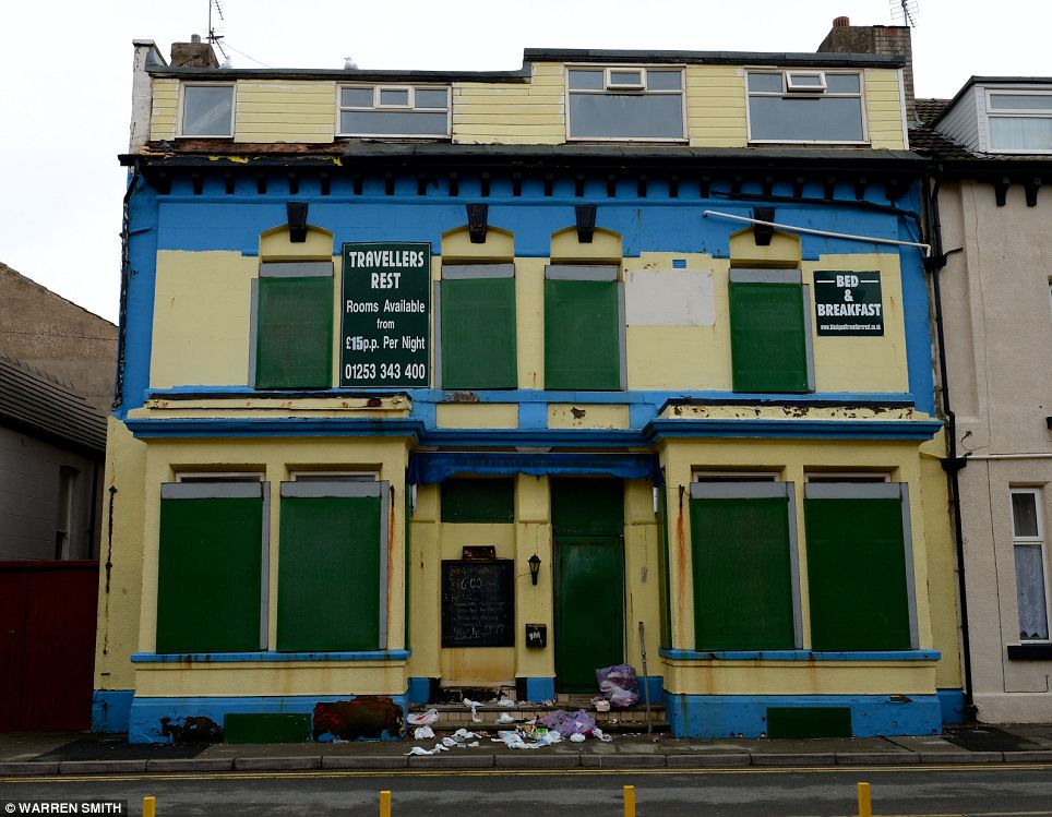 Forlorn: Rubbish lies heaped on the steps of the closed-down Travellers Rest guest-house, where a sign reveals its owners' last-ditch attempt to revive their business