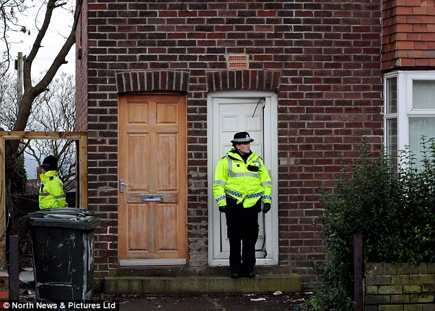 Probe: Police outside one of the homes which was raided as part of the investigation