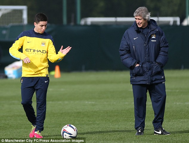 All set: Pellegrini chats to Samir Nasri (left) as City train ahead of the trip to Wembley