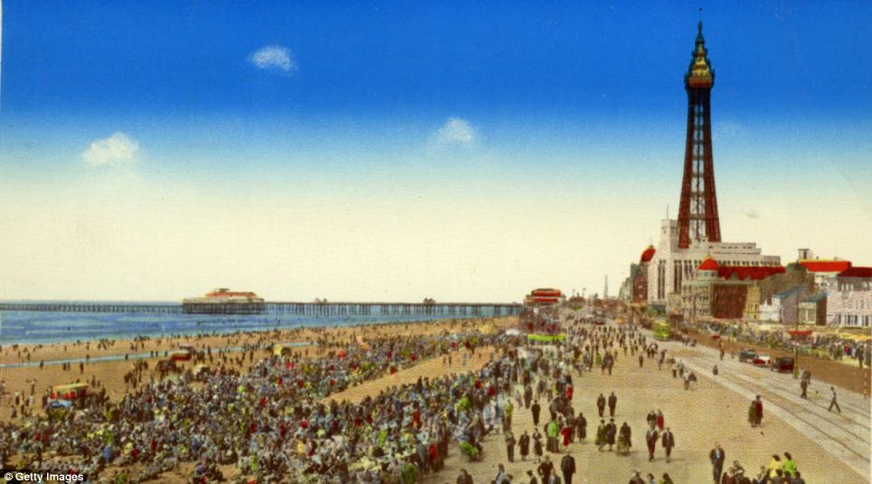 Enjoying a bit of sun: Crowds roam the beach and boardwalk on a summer's day at Blackpool in 1935