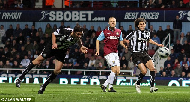 Best of enemies: Carroll (left) scores another goal against his current club back in 2010