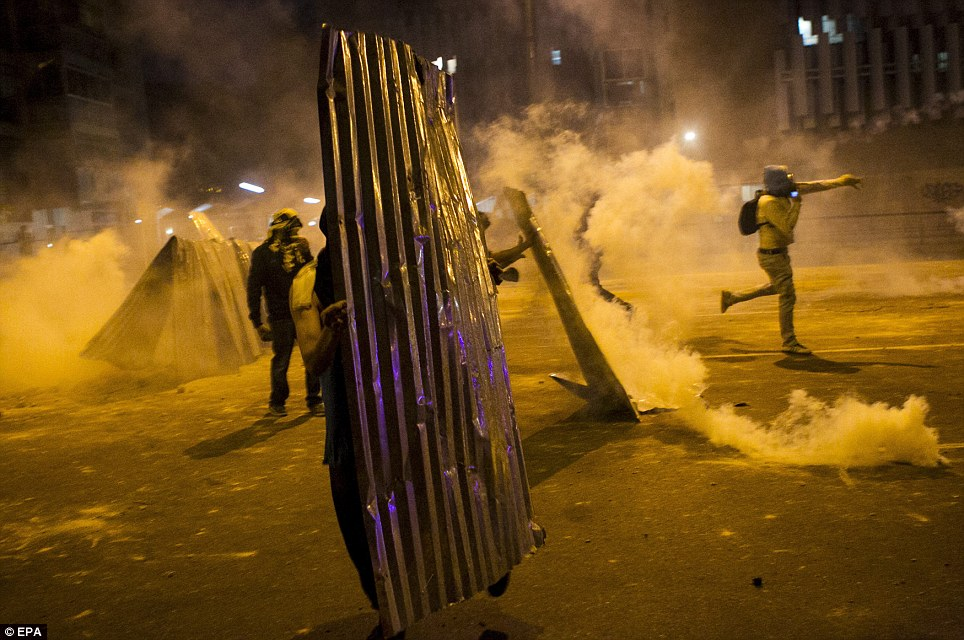 Clashes: Protesters struggled against the effects of tear gas last night. Between 20 and 41 were arrested by the authorities