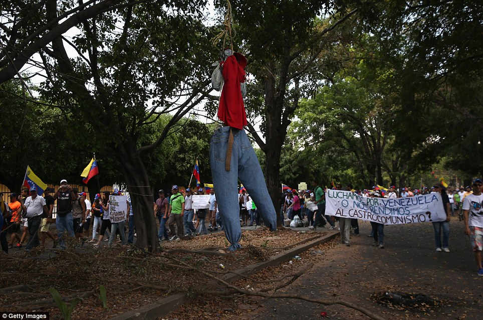 Hate figure: The protesters fashioned an effigy of President Nicolas Maduro today as a march passed through a residential neighborhood in Valencia, Venezuela