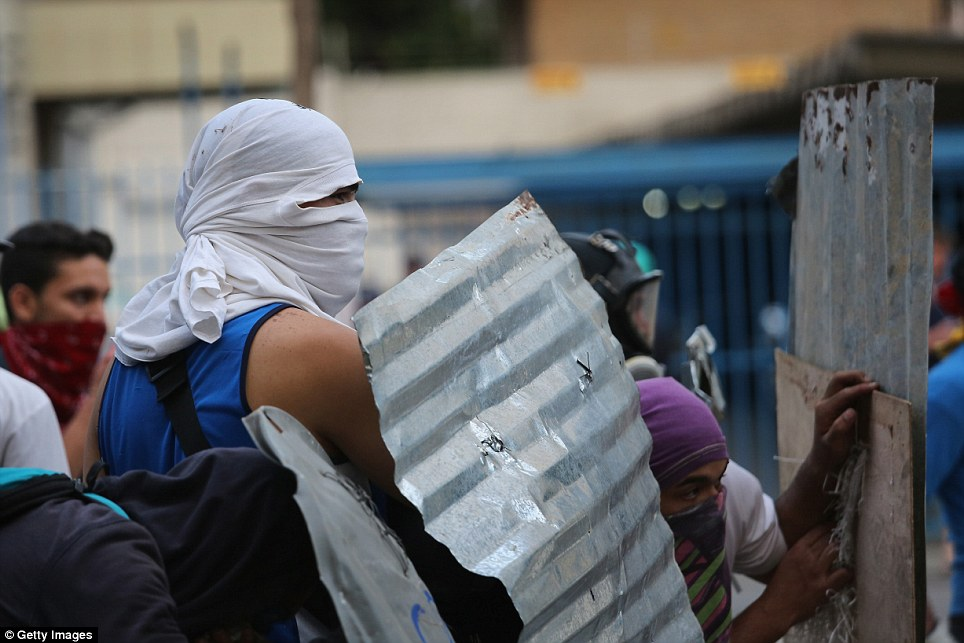 Protection: Demonstrators have covered their faces with fabric and fashioned home-made shields out of sheets of corrugated metal
