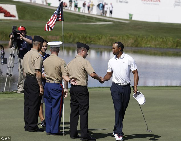 Right stuff: Woods, right, shakes hands with military personnel on the 17th green