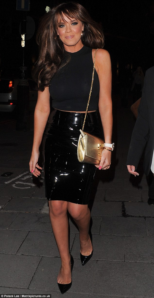 First it's black: The glamour model is pictured leaving Beyonce's Mrs Carter World Tour gig at the O2 in a short top and shiny skirt bearing a glimpse of midriff