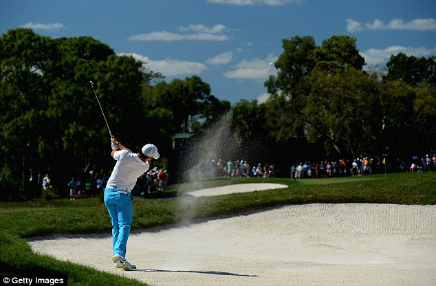 Bunkered: McIlroy plays out of the sand on the second hole at the PGA National Resort and Spa in Florida