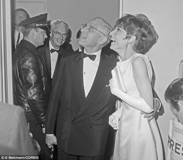05 Apr 1965 ---  Oscar Winner, for Best Achievement in Directing, and the star of his film, Audrey Hepburn, watch TV monitor in press room at the 37th Annual Academy Awards and learn that their picture, 'My Fair Lady,' has just been named for Best picture