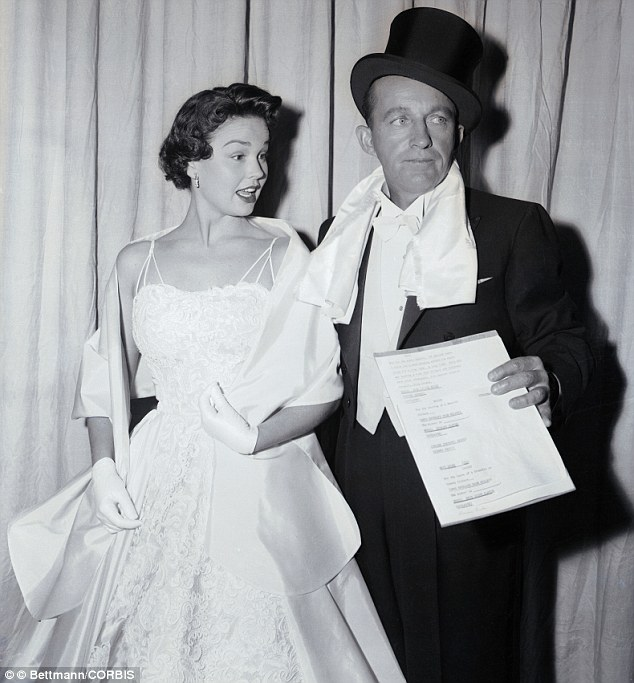 30 Mar 1955--- Bing Crosby pulled a real switch as he made his appearance at the 27th Annual Academy Awards wearing a top hat and tails. With the famous crooner is his date Kathryn Grant