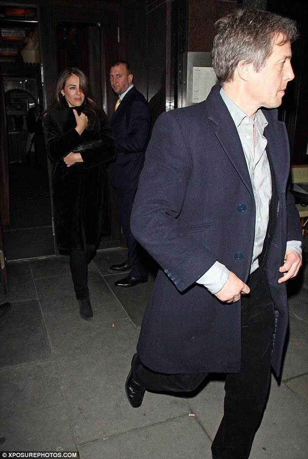 Leading gentleman: Hugh lead Liz to their car on Saturday night, looking dapper in a blue pea coat