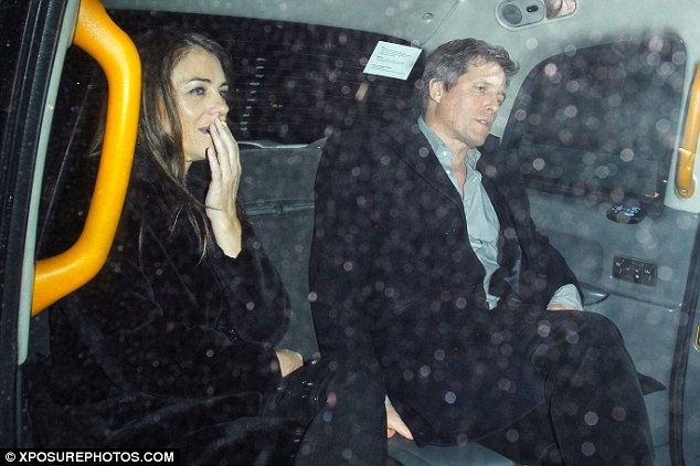 Get going: Hugh beckoned at the driver to begin their journey as they jumped in the car