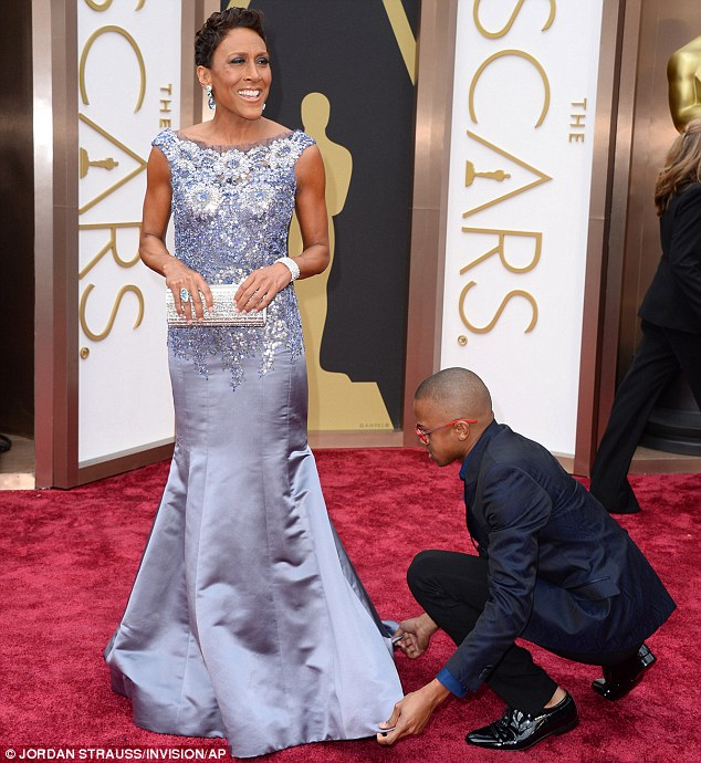 Almost ready! GMA anchor Robin Roberts gets a last minute adjustment on the red carpet at the 2014 Academy Awards