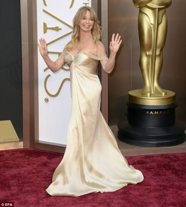 Playful mother: Private Benjamin star Goldie looked considerably more youthful in a golden silk gown with a fitted bodice and draped shoulder details as she played up for the cameras and showed off her fantastic figure