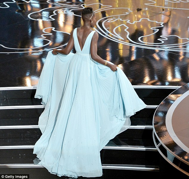 Making an entrance: Lupita lifts her Prada gown to make sure she doesn't trip on her way to the stage