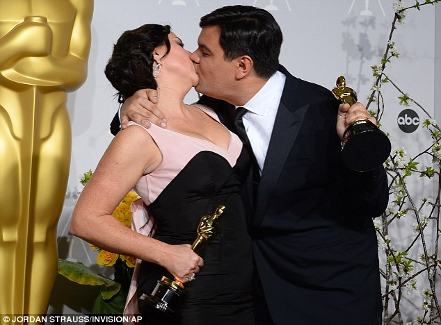 Best Smooch: Couple Kristen Anderson-Lopez, left, and Robert Lopez kiss in the press room with their awards for Best Original Song for Let It Go from Frozen