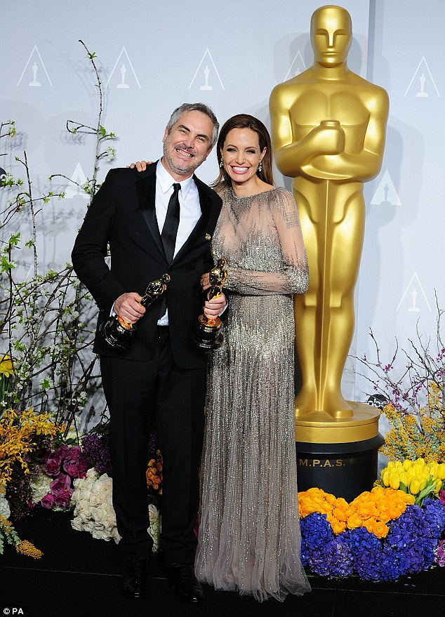 Party time: Alfonso Cuaron - winner of the Best Director award for Gravity - poses with Angelina Jolie in the press room of the 86th Academy Awards