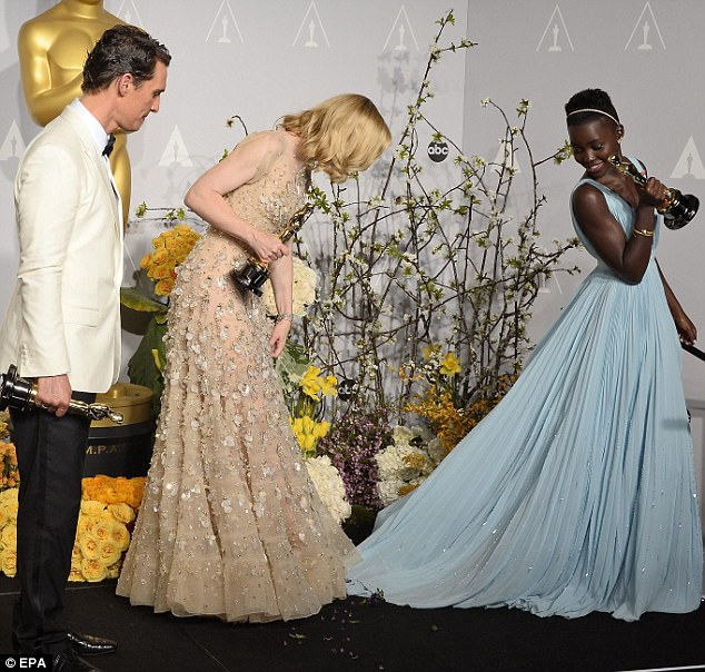 Watch my dress! Cate almost steps on Lupita's gown as they pose together backstage