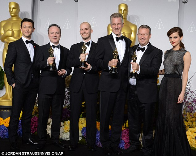 Gravity wins again: Presenters Joseph Gordon-Levitt, left, and Emma Watson, right, pose with Tim Webber, David Shirk, Chris Lawrence, and Neil Corbould with the award for Best Visual Effects
