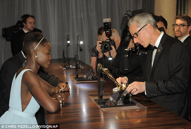 Exciting moment: Lupita watches as her statue is engraved the Governors Ball after the Oscars