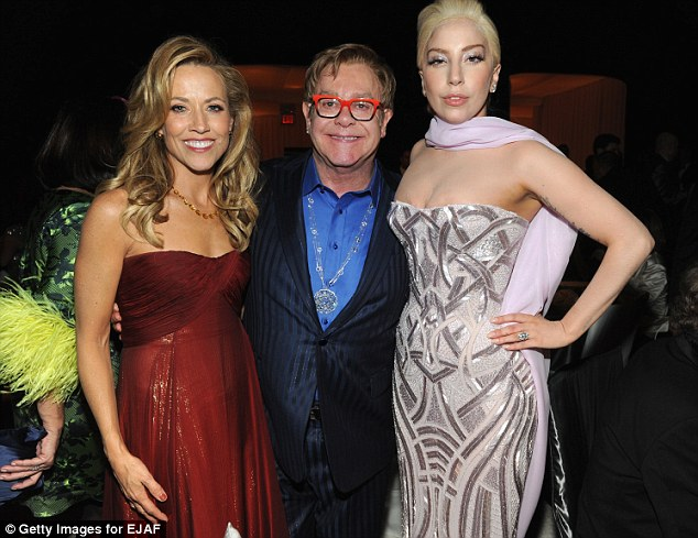 Muscling in: The singer made sure she had her picture taken with all the stars including Elton John (centre) and Sheryl Crow