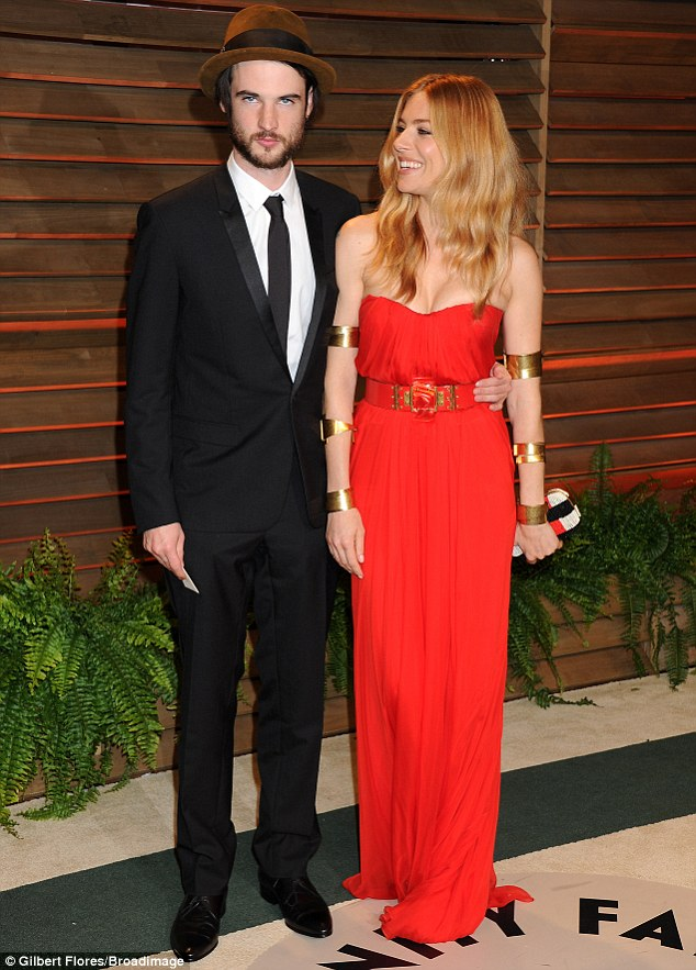 Oh, Sienna! A smiling Ms Miller looked great in red and gold but boyfriend Tom Sturridge looked pretty intense