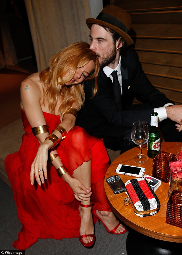 Cute: Tom Sturridge and Sienna Miller share a sweet moment at the party