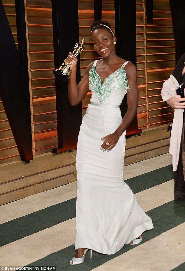 Check out my man! Lupita Nyong'o hols her Oscar up with pride