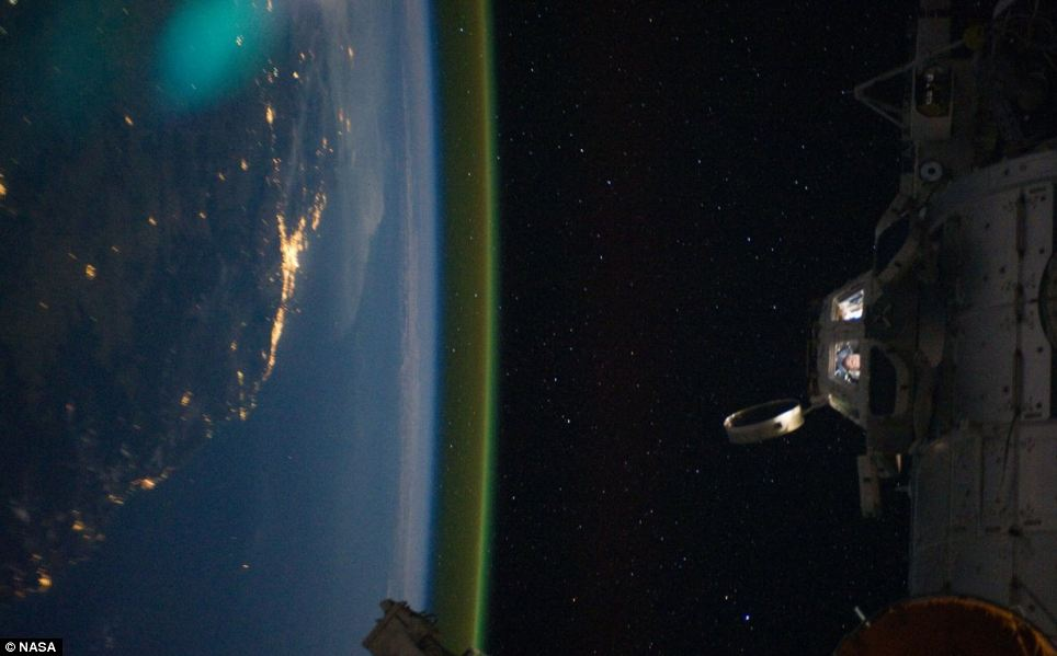 This unique photographic angle, featuring the International Space Station's Cupola and crew activity inside it, other hardware belonging to the station, city lights on Earth and airglow was captured by one of the Expedition 28 crew members. The major urban area on the coast is Brisbane, Australia. The station was passing over an area southwest of Canberra