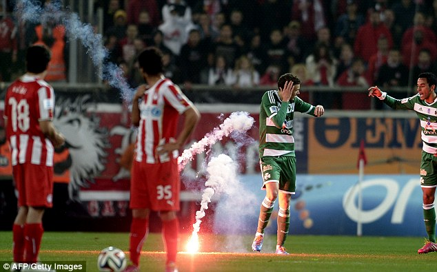 Tension: A flare thrown by Olympiakos supporters hits Panathinaikos' Marcus Berg (centre)