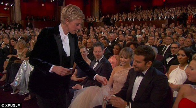 Ellen DeGeneres gives an early hint that it wasn't American Hustle's night  by handing Bradley Cooper some consolation scratch cards for losing out on Best Supporting Actor - one of her many welcome forays amongst the star-studded audience